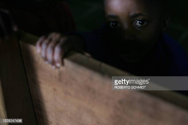 Kikuyu boy looks from behind a church bench in a monastery that hundreds of displaced are using as a camp high in the mountains some 10 km from the...