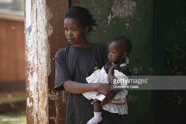 A Kikuyu woman and her daughter watch the men from their family pack up their belongings as they leave their house fearing attacks from the Kalenjin...