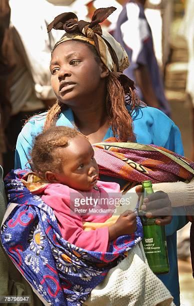 Kikuyu woman carries her baby as she arrives at the Nakuru show ground on January 7 2008 in Nakuru Kenya Local volunteers and charities are helping...