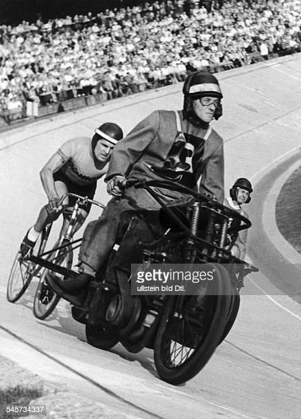 Kilian Gustav *Bahnradsportler Trainer D waehrend eines Radrennens hinter seinemSchrittmacher in der Halle 1953