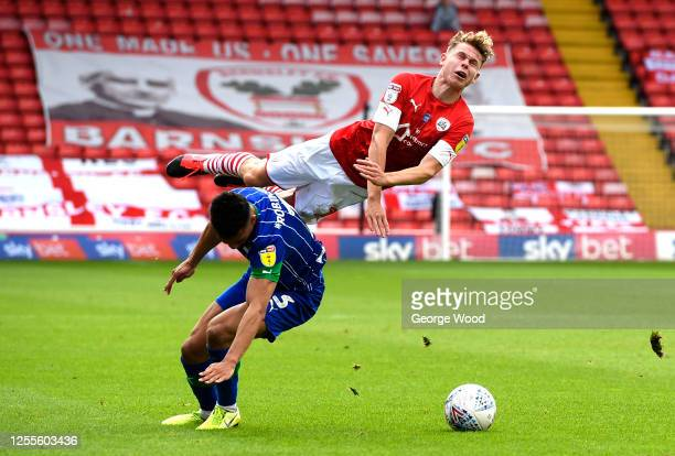 Kilian Ludewig of Barnsley is tackled by Antonee Robinson of Wigan Athletic during the Sky Bet Championship match between Barnsley and Wigan Athletic...