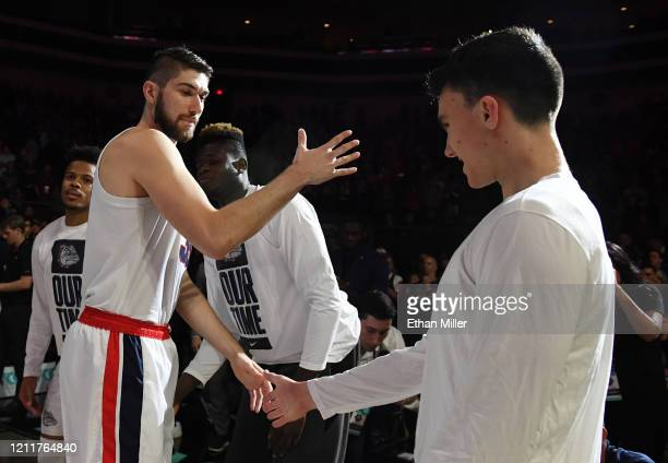 Killian Tillie of the Gonzaga Bulldogs is greeted on the court by Matthew Lang during player introductions before taking on the Saint Mary's Gaels in...