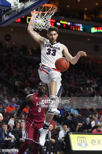 Killian Tillie of the Gonzaga Bulldogs dunks in front of Eli Scott of the Loyola Marymount Lions during a quarterfinal game of the West Coast...