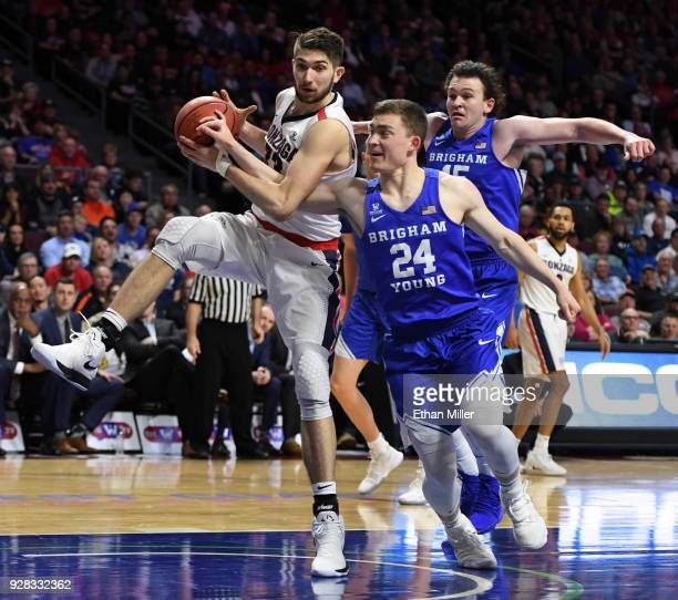 Killian Tillie of the Gonzaga Bulldogs is fouled as he drives to the basket against McKay Cannon and Payton Dastrup of the Brigham Young Cougars...
