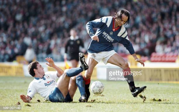 Kilmarnock player Craig Paterson slides in to challenge Mark Hately of Rangers during a Scottish Premier Division match at Ibrox on October 15, 1994...