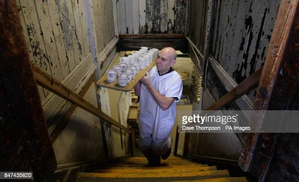 Kiln Man Placer Dennis Robinson carries mugs on a wareboard as he works on Burleigh's Jubilee ware at Middleport Pottery in Burslem StokeonTrent