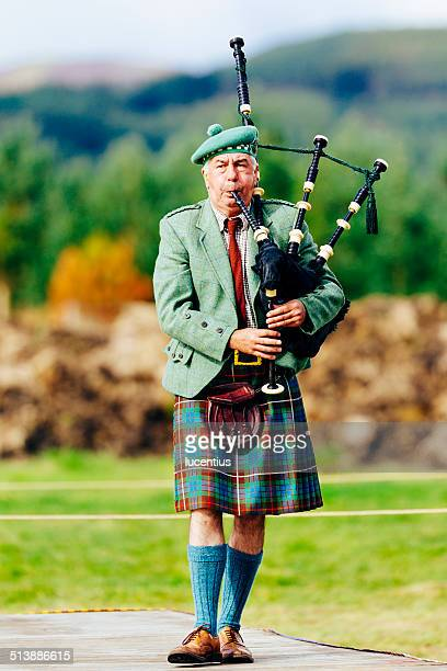 kilted male scottish piper with bagpipes - kilt stock photos and pictures