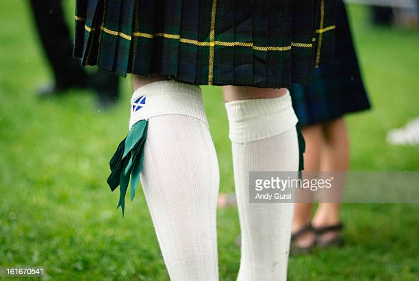 CONTENT] Kilted man's legs in a dark green tartan with white stockings with green flashes Scottish StAndrews flag is visible on the stockings...