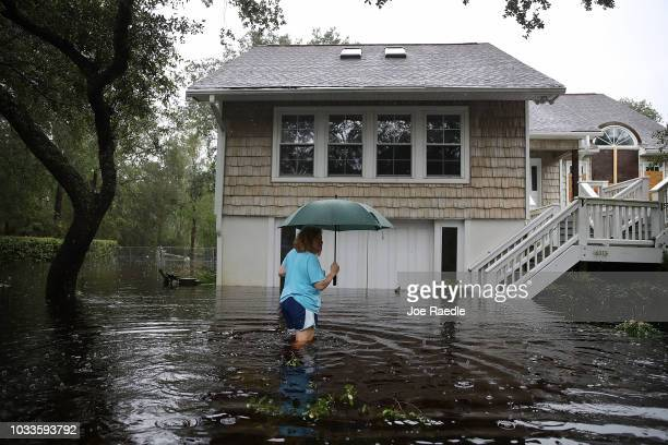 Kim Adams makes her way to her home that is surrounded by flood waters after Hurricane Florence passed through the area on September 15, 2018 in...