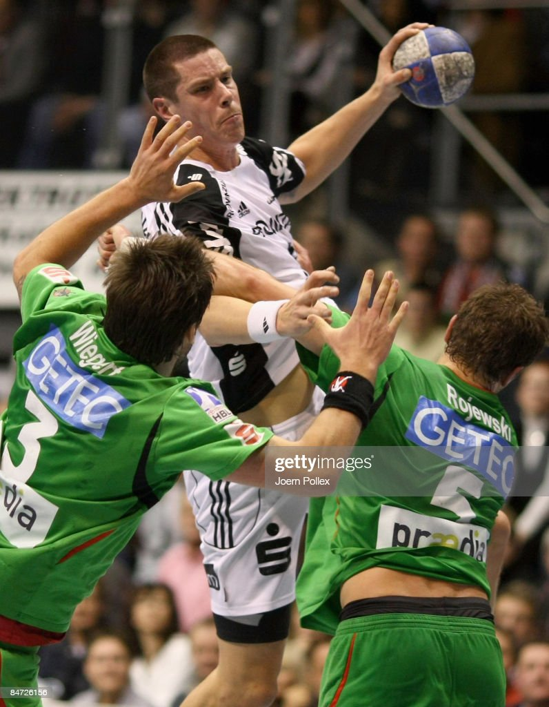Kim Andersson of Kiel (C) is attacked by Bennet Wiegert (L) and Andreas Rojewski (R) of Magdeburg during the Toyota Handball Bundesliga match between SC Magdeburg and THW Kiel at the Boerdeland hall on February 10, 2009 in Magdeburg, Germany.