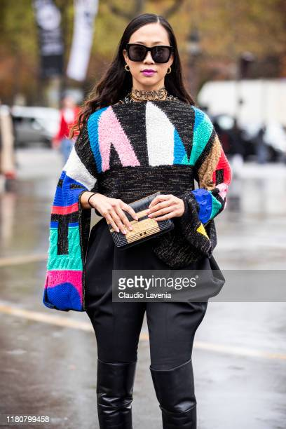 Kim Bui Kollar, wearing a colorful sweater, black pants, black boots and Chanel bag, is seen outside the Chanel show during Paris Fashion Week -...