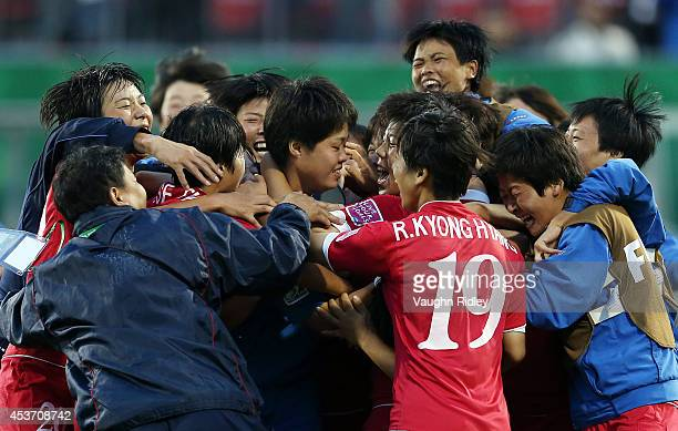 Kim Choi Ok of Korea DPR is mobbed by teammates after making three saves in the shoot out during the FIFA U20 Women's World Cup Canada 2014 Quarter...