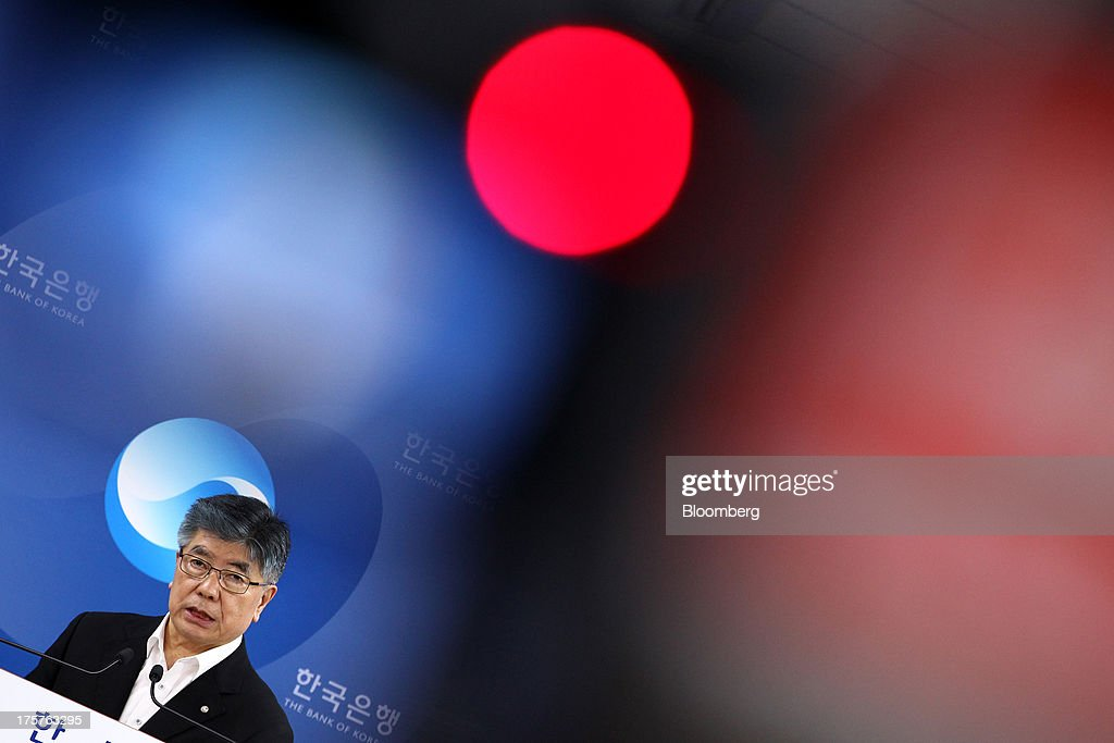 Kim Choong Soo, governor of the Bank of Korea, is photographed behind the light of a video camera during a news conference following a monetary policy meeting at the central bank's headquarters in Seoul, South Korea, on Thursday, Aug. 8, 2013. The Bank of Korea held its benchmark interest rate steady, as signs of stronger growth in the U.S. back its view that the economy will gather momentum. Photographer: SeongJoon Cho/Bloomberg via Getty Images