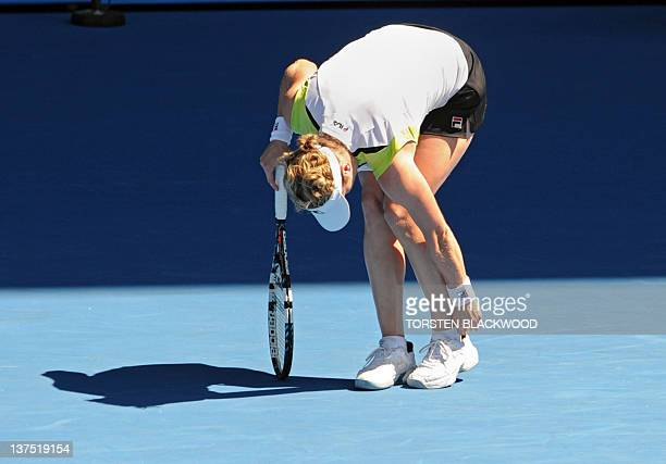Kim Clijsters of Belgium adjusts her sock after slipping on the court while playing against Li Na of China in their fourth round women's singles...