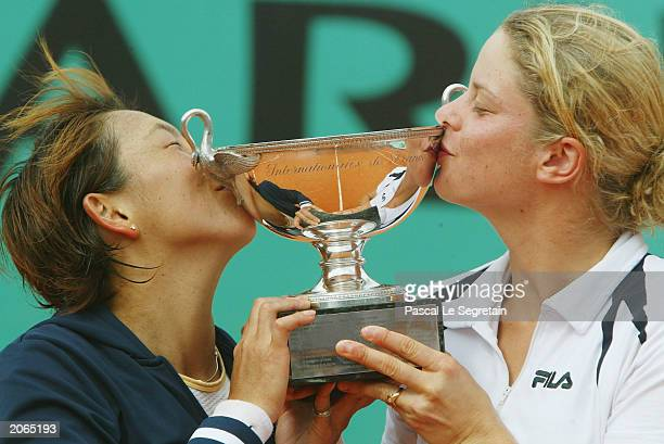 Kim Clijsters of Belgium and Ai Sugiyama of Japan with the trophy after winning their womens doubles final match against Virginia Ruano Pascual of...