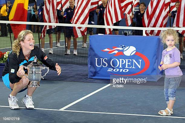 Kim Clijsters of Belgium holds the championship trophy as she is joined by her daughter Jada after defeating Vera Zvonareva of Russia during their...