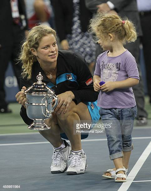 Kim Clijsters of Belgium holds the championship trophy as she is joined by her daughter Jada after Clijsters defeated Vera Zvonareva of Russia during...