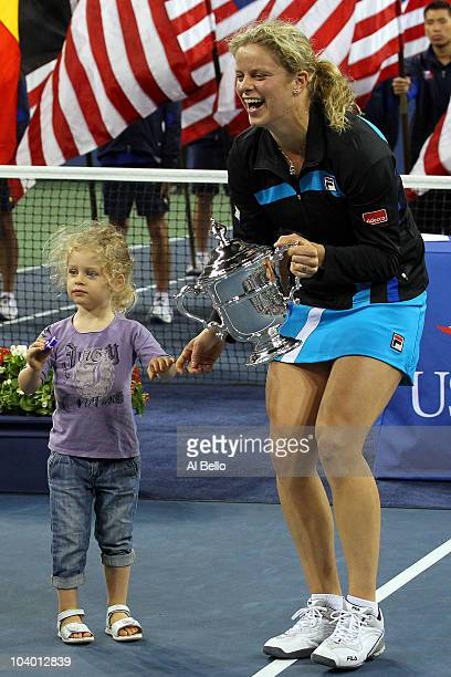 Kim Clijsters of Belgium holds the championship trophy as she celebrates with her daughter Jada after defeating Vera Zvonareva of Russia during their...