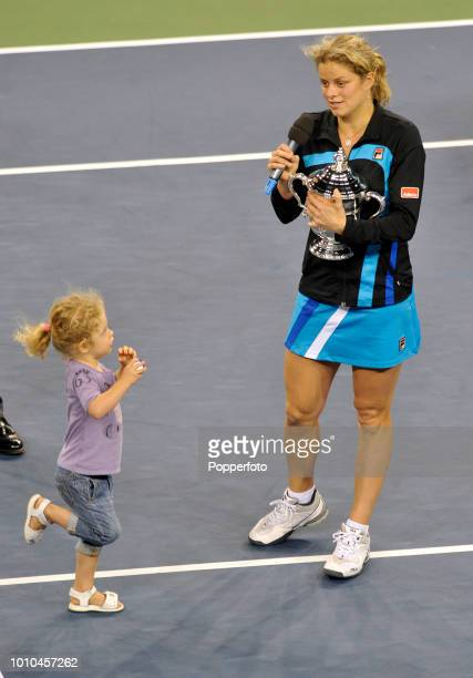 Kim Clijsters of Belgium holds the trophy whilst watching her daughter Jada after her victory over Vera Zvonareva of Russia following the Ladies'...