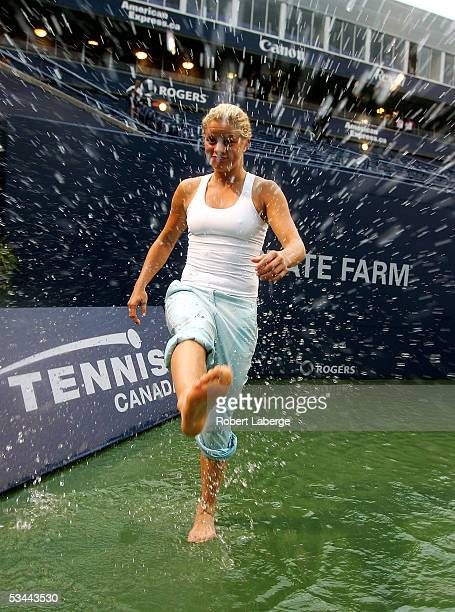Kim Clijsters of Belgium kicks water at photographers on center court after torrential rains delayed play during the match between Amelie Mauresmo of...