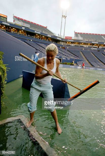 Kim Clijsters of Belgium plays with a squeegee on center court after torrential rains delayed play during the match between Amelie Mauresmo of France...