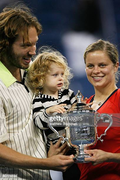Kim Clijsters of Belgium poses with the championship trophy alongside husband Brian Lynch and daughter Jada after defeating Caroline Wozniacki of...