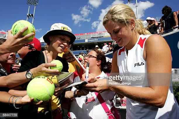 Kim Clijsters of Belgium signs the passeport of Belgian spectator Kristin Van De Vijver after defeating Justine HeninHardenne of Belgium 75 61 in the...
