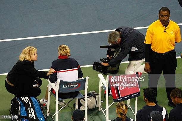 Kim Clijsters of Belgium sits with tournament official Donna Kelso after the Women's Singles Semifinal match in which Serena Williams was...