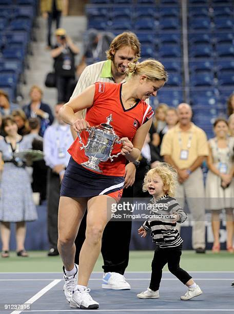 Kim Clijsters of Belgium with the championship trophy alongside husband Brian Lynch and daughter Jada after defeating Caroline Wozniacki of Denmark...