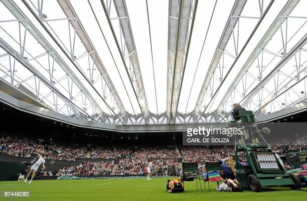 Kim Clijsters serves during her exhibition mixed doubles match against Andre Aggassi and Steffi Graf to mark the launch of the new retractable roof...