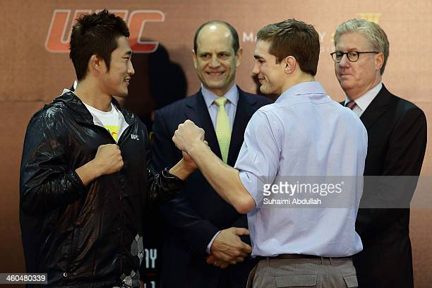 Kim Dong Hyun of South Korea and John Hathaway of England face off as Mark Fischer, Managing Director of UFC Asia and Edward M. Tracy, President and...