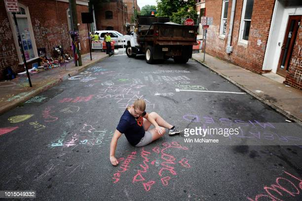 Kim Ganczak writes on the street with chalk near a makeshift memorial for Heather Heyer who was killed one year ago tomorrow during a deadly clash...