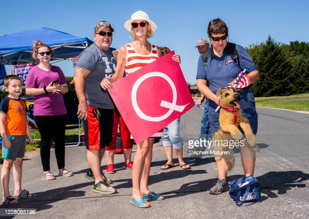 Kim Harty holds a Q Anon sign outside Mankato Regional Airport as President Donald Trump makes a campaign stop on August 17, 2020 in Mankato,...