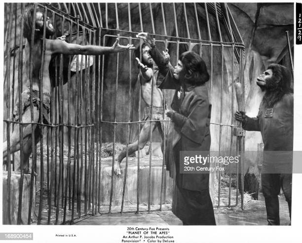 Kim Hunter studies human captives while Buck Kartalian looks on in a scene from the film 'Planet Of The Apes' 1968