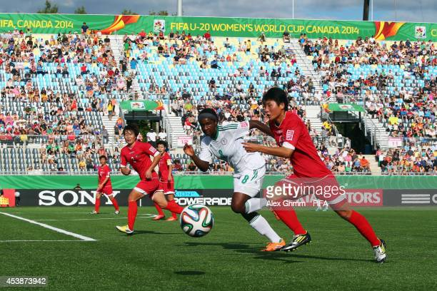 Kim Hyang Mi of Korea DPR is challenged by Courtney Dike of Nigeria during the FIFA U20 Women's World Cup Canada 2014 Semi Final match between Korea...