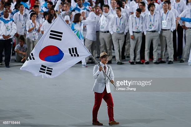 Kim Hyeon Woo of South Korea carries the country's flag during the opening ceremony ahead of the 2014 Asian Games at Incheon Asiad Stadium on...
