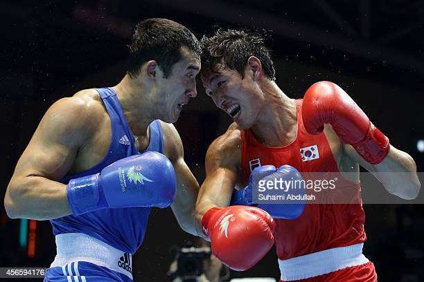 Kim Hyeongkyu of South Korea fights Adilbek Niyazymbetov of Kazakhstan during the men's light heavy weight bout final on day fourteen of the 2014...