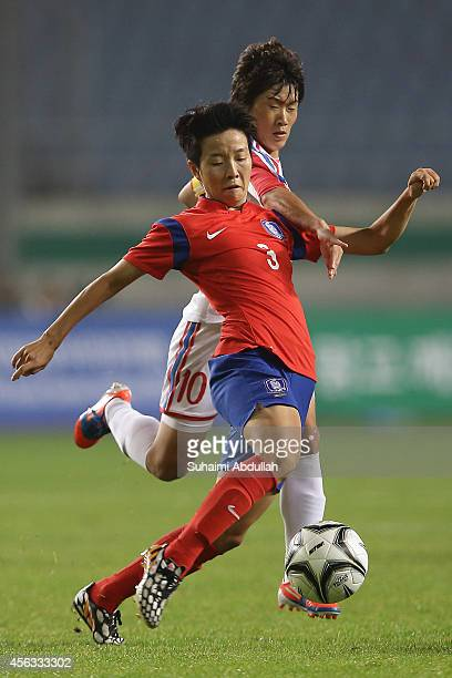 Kim Hyeri of South Korea and Ra Unsim of North Korea challenge for the ball in the Women's Football Semifinal Match on day ten of the 2014 Asian...