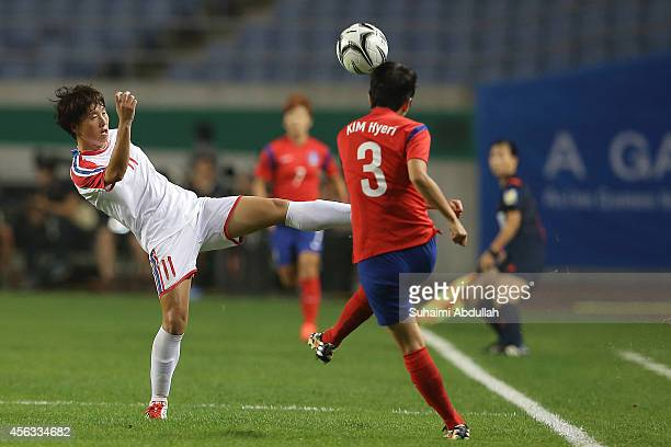 Kim Hyeri of South Korea shoots past Ri Regyong of North Korea during the Women's Football Semifinal Match on day ten of the 2014 Asian Games at...