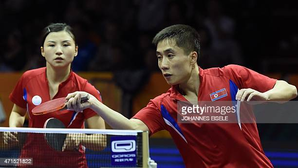 Kim Hyok Bong and Kim Jong of North Korea serve during their mixed double quarter final match against Yan An and Wu Yang of China at the 2015 World...