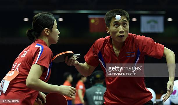 Kim Hyok Bong and Kim Jong of North Korea serve during their mixed doubles quarter final match against Yan An and Wu Yang of China at the 2015 World...
