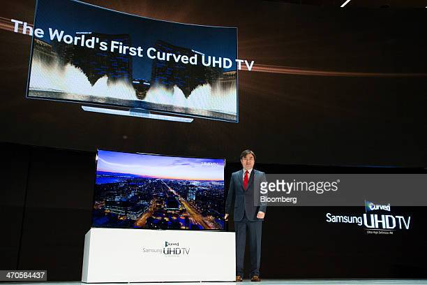 Kim Hyun Suk executive vice president of the visual display unit at Samsung Electronics Co poses with one of the company's curved Ultra High...
