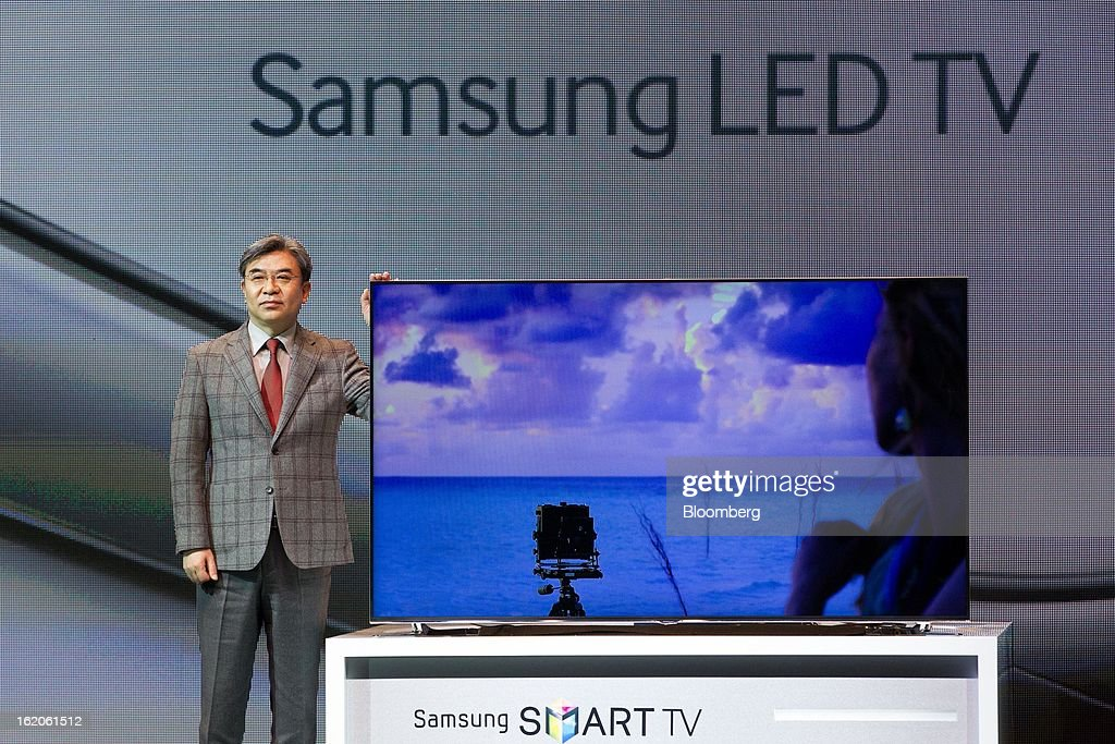 Kim Hyun Suk, vice president of visual display at Samsung Electronics Co., poses with one of the company's F8000 series smart televisions during a media event in Seoul, South Korea, on Tuesday, Feb. 19, 2013. Samsung Electronics Co., the world's largest television maker, targets to start selling TVs using a technology allowing brighter and sharper images in the first half to extend its market lead. Photographer: SeongJoon Cho/Bloomberg via Getty Images