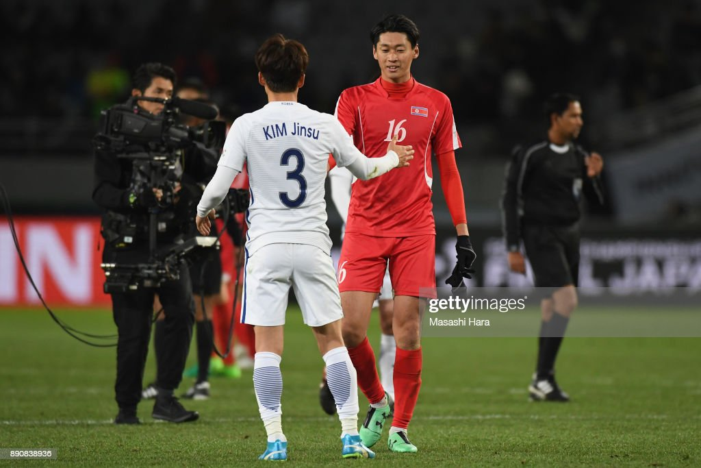 Kim Jinsu of South Korea and Ri Yong Jik of North Korea embrace after the EAFF E-1 Men's Football Championship between North Korea and South Korea at Ajinomoto Stadium on December 12, 2017 in Chofu, Tokyo, Japan.