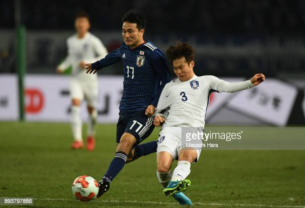 Kim Jinsu of South Korea and Yasuyuki Konno of Japan compete for the ball during the EAFF E1 Men's Football Championship between Japan and South...