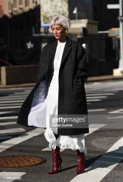 Kim Jones is seen wearing a gray and black coat and white dress outside the Self Portrait show during New York Fashion Week Fall/Winter 2019 on...