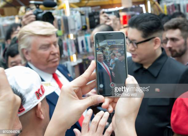 Kim Jong Un and Donald Trump impersonators Howard X and Dennis Alan are surrounded by onlookers as they arrive for a promotional event on June 9 2018...
