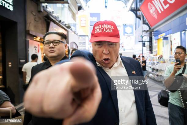 Kim Jong Un impersonator Howard X and Donald Trump impersonator Dennis Alan walk through a shopping district on June 24 2019 in Osaka Japan Leaders...