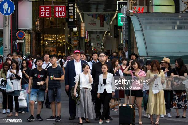 Kim Jong Un impersonator Howard X and Donald Trump impersonator Dennis Alan wait to cross a road as they walk through a shopping district on June 24...