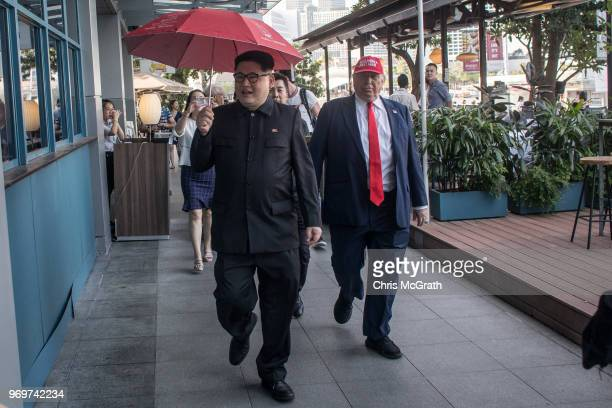 Kim Jong Un impersonator Howard X and Donald Trump impersonator Dennis Alan walk around greeting people during a visit to the famous Merlion Park on...
